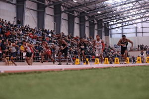 Male track athletes compete on indoor track